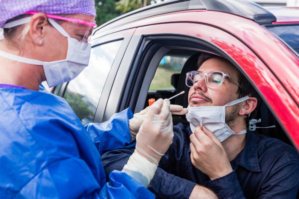 Man receiving a Coronavirus test from a nurse