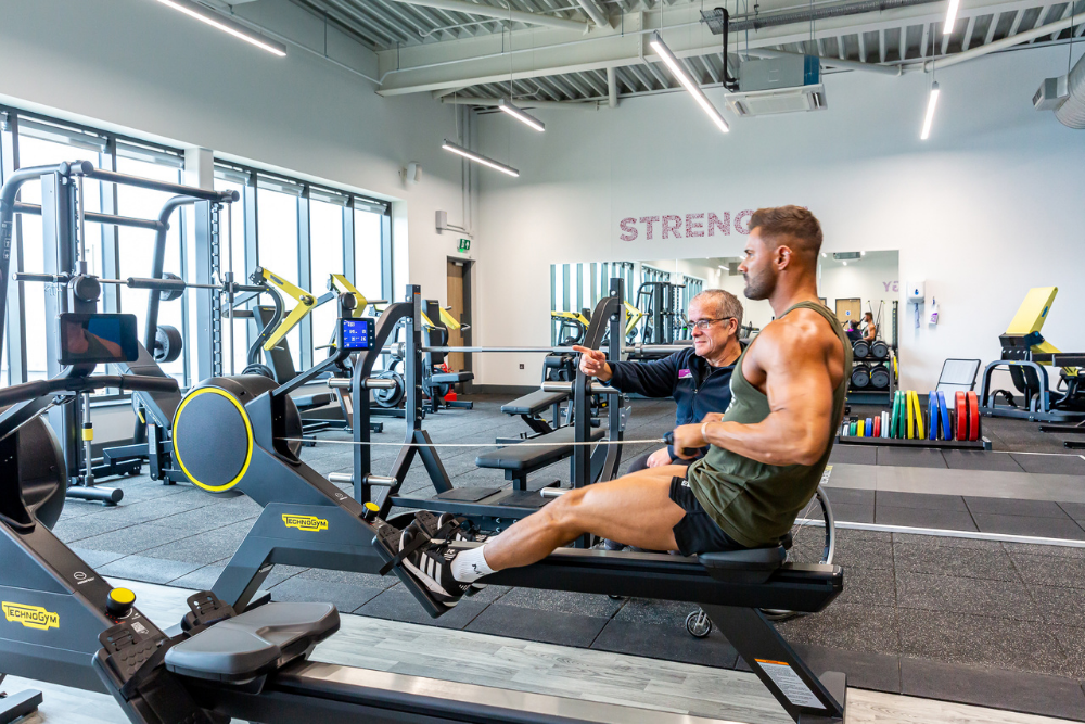 Man on rowing machine in the gym with an instructor